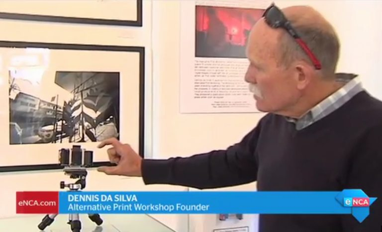 eNCA TV screenshot capture, 11 June 2017. Dennis da Silva, Alternative Print Workshop, explaining how matchbox pinhole camera works